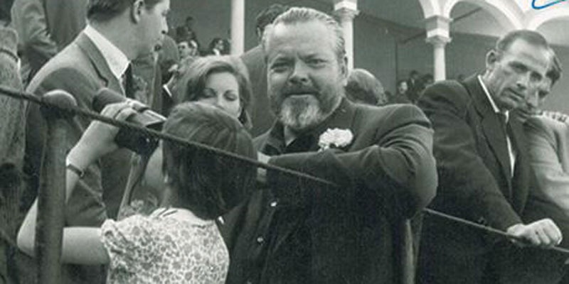 Beatrice Welles looks through binoculars into the crowd as her father, Orson Welles, looks at the camera at annual bullfight at the Feria de Sevilla in Spain, April 1964.