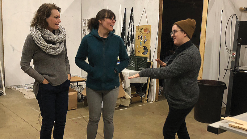 Left to right: Meghan Shein, Jessica Tenbusch and Elize Jekabsen stand in the shared metal and woodworking shop.